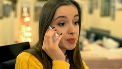 Girl sitting in the cafe and having an argument through cellphone, steadycam sho Stock Footage