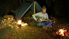 4k . Tourist music  life. Man traveler, near  campfire  and tent tunes  guitar. Stock Footage