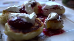 Close-up cheese pancakes with berry jam and sour cream. Eating with spoon. Slow Stock Footage