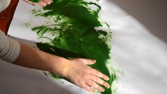 Girl smears paint on paper Stock Footage