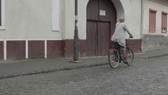 Blonde woman riding a bike on a street paved with stone Stock Footage