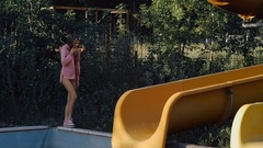 Attractive young girl dressed in a swimsuit posing in an abandoned aquapark Stock Footage