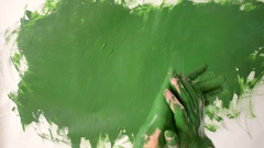 Girl smears green paint on the hands and draws on paper Stock Footage