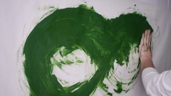 Woman smears draws green paint on a white surface Stock Footage