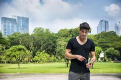 Handsome young man outdoors in city park Stock Photos