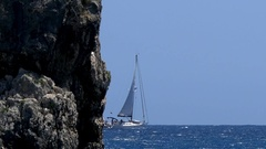 Sailboats leaving after a rock rose from the sea and away to sea on blue wate Stock Footage