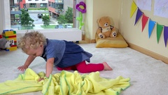 Mischievous toddler girl hide under yellow plaid blanket on floor Stock Footage