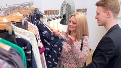 Young couple chosing clother in store Stock Footage