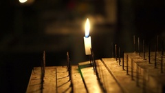 Single candle lit in the dark. Moving flame on sacred stand Stock Footage