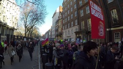 4K Crane Shot of US Embassy London anti Trump protesters passing by Stock Footage