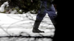 Man going through pine forest on a road covered with snow Stock Footage