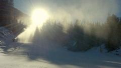Powerful cannon spreading fresh snow on ski slope Stock Footage