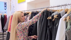 Shopping of Young blonde woman chosing clother Stock Footage