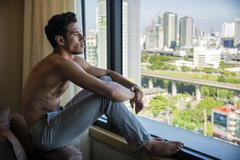 Sexy young man sitting shirtless by curtains Stock Photos