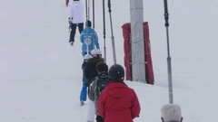 Skiers climb next to the ski using a steel telesky Stock Footage