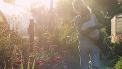 Older brother holds of young brother goes outdoor next to the flowers in the Stock Footage