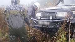11. 10. 16, Russia, Novosibirsk, Salair Rubilovo. Men pull the big Jeep from Stock Footage