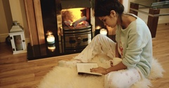 Cute teenage girl is reading a book beside the fireplace. Red Epic. 4k Stock Footage