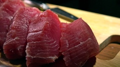 Cut tuna fillet pieces on wooden board. 4K close-up dolly video Stock Footage