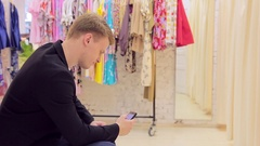 Young man waiting for his girlfriend near the fitting room in a clothing store Stock Footage