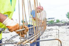 Construction worker binding rebar for reinforce concrete column at the buil.. Stock Photos