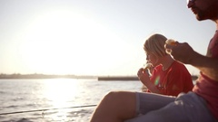Two blonde boys sitting with his father in hat and sunglasses near sea fishing Stock Footage