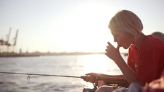 Young Caucasian blonde boy sitting with fishing rod near sea licking fingers in Stock Footage