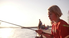 Young Caucasian blonde kid in red shirt holding fishing rod sitting with his Stock Footage