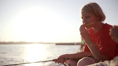 Young Caucasian kid in red t-shirt fishing sitting on pier eating melon in Stock Footage