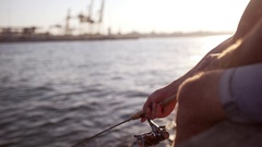 Close up footage of man's hands with fishing rod near sea with port on Stock Footage