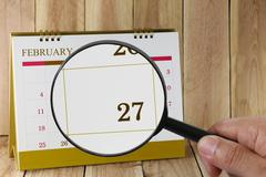 Magnifying glass in hand on calendar you can look Twenty seven day of month.. Stock Photos
