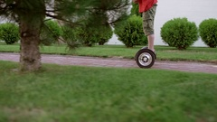 Caucasian boy in red t-shirt and military shorts driving gyroscooter through Stock Footage