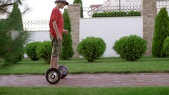 Young Caucasian boy in red t-shirt military shorts and hat driving gyroscooter Stock Footage