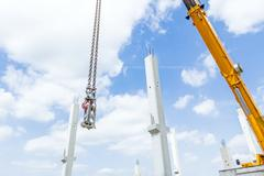 Crane hook swinging above on chains, cloudy sky is in background Stock Photos