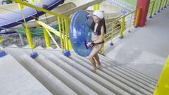Girl with rubber ring going to ride on waterpark slide Stock Footage
