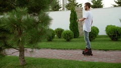 Caucasian male with beard wearing glasses jeans and white t-shirt rollerblading Stock Footage