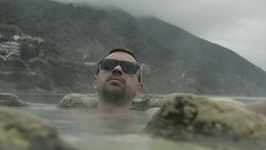Young Man Takes a Hot Mineral Bath on the Beach at the Resort Stock Footage