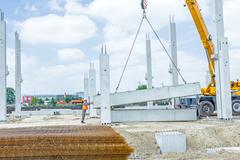 Mobile crane is carry concrete joist to assembly huge hall. Workers are hel.. Stock Photos