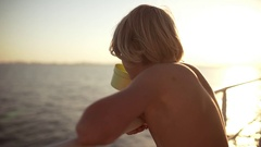 Young blonde Caucasian boy drinking water from plastic yellow cup leaning on Stock Footage