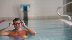 Wet sportsman corrects his goggles in the swimming pool Stock Footage