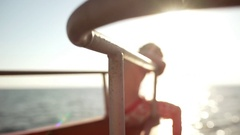 Close up footage of bow deck of ship with blonde boy sitting on it while sun Stock Footage