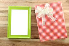 Red gift box with empty wooden picture frame on wood background. Stock Photos