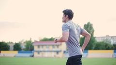 Man running on athletics running track on stadium Stock Footage