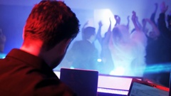 DJ Sitting in Front of the DJ Console Seen from the Back. Wedding party Stock Footage