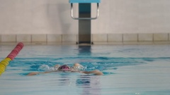 The woman in goggles training swimming crawl in the blue pool Stock Footage