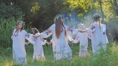 A group of young people in national Slavic costumes dance in a circle around the Stock Footage
