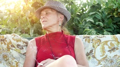 Smiling mature woman in hat sitting in the garden smoking cigarette. 3840x2160 Stock Footage