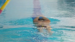 Young sportsman training to swim butterfly in the blue swimming pool Stock Footage