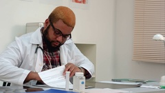Afroamerican physician filling in medical forms and answering phone calls at his Stock Footage