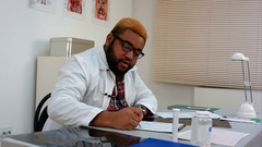 Afroamerican male physician tired after long working day in hospital Stock Footage